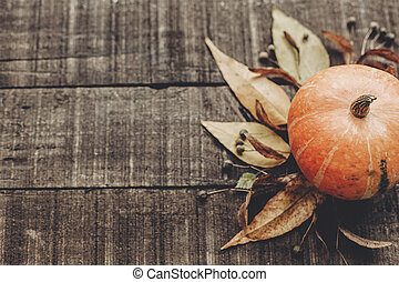thanksgiving or halloween concept greeting card. beautiful pumpkin with leaves and berries on rustic wooden background, top view. space for text. cozy autumn mood. fall holiday