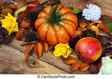 Thanksgiving orange pumpkin, apple, pine cones wreath, close up