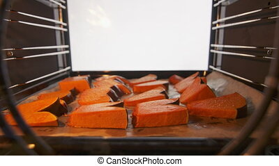 Roasting sliced pumpkin pieces inside the oven.