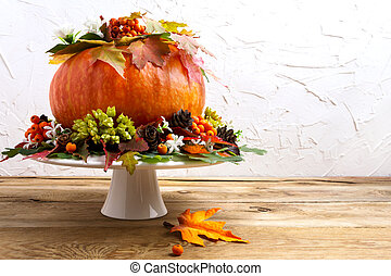Thanksgiving rustic table centerpiece with pumpkin, colorful leaves, berries, seeds and cones, copy space. Fall greeting background.
