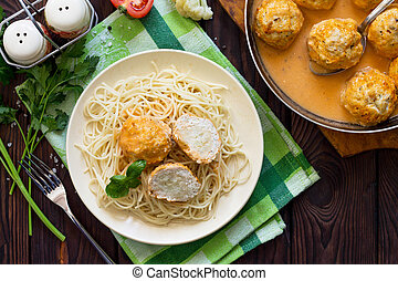 Thanksgiving Turkey dinner. Meat balls turkey with cauliflower in tomato sauce and spaghetti on a wooden table. Copy space, top view flat lay background.