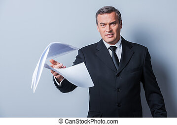 That is all wrong! Furious mature man in formalwear throwing documents while standing against grey background