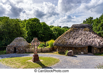 Thatch and stone cottage with Celtic cross in centre, concept of early age human settlement