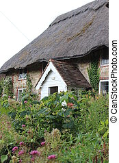 Thatched cottage in rural England in summer.
