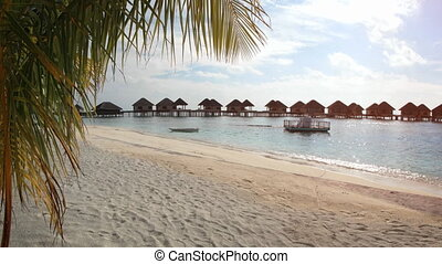 Thatched Roof Bungalows on a Pier at a Tropical Resort -...