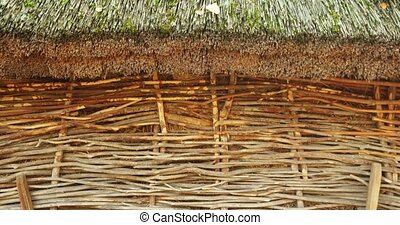 Traditional storage shed with a neatly trimmed, thatched roof, constructed for hay storage on a rural farm in Ukraine. 4k DCI stock footage