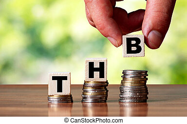 THB Thai currency word symbol - business concept. Hands put wooden block on stacked increasing coin.