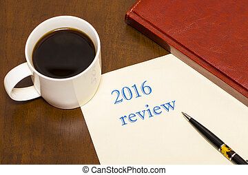 The 2016 review the text on the sheet of paper next to a Cup of coffee, business diary on wooden table