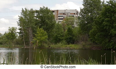 The abandoned building is located among the trees. There is...