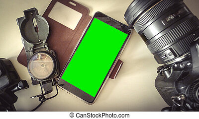 the accessories to travel on table defocus ,camera compass and blank mobile phone, Top view copy space