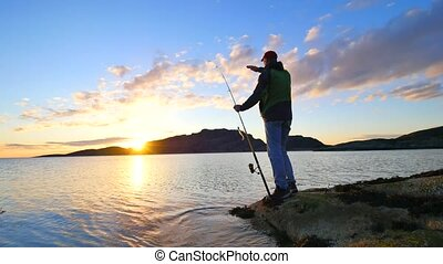 The active man is fishing on sea from the rocky coast. Fisherman check pushing bait on the fishing line, prepare rod and than throw lure into peacefull water. Fisherman silhouette at sunset