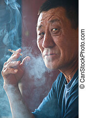 The adult man the Asian sit and smokes a cigarette