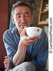 The adult person the native of Asia drinks tea from a cup -...