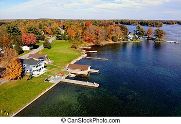 The aerial view of the waterfront homes with private docks surrounded by stunning fall foliage near Wellesley Island, New York, U.S.A