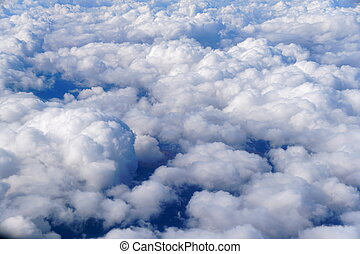 The aerial view of white clouds above the blue sky