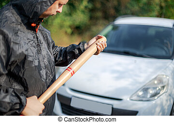 The aggressive person with the baseball bat in front of the car