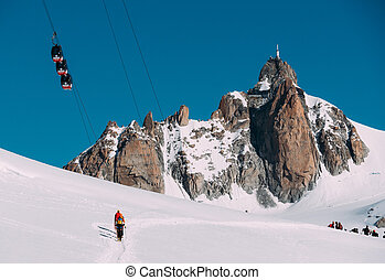 The Aiguille du Midi peak with Panoramic Mont-Blanc cable car; in foreground a group of mountaineers. Mont Blanc massif, Chamonix, France, Europe.