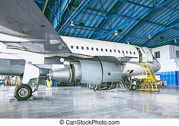The aircraft is in the aviation hangar. Theme repair and maintenance of airplane airlines.