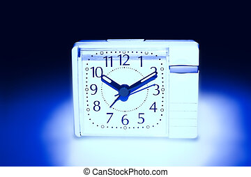 the alarm clock of white color is illuminated from beneath dark blue by light on a white background