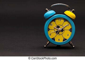 Alarm clock on black background.