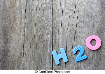 The Alphabet of H2O Lay on old brown wood floor background.