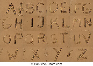 The Alphabet Written In Sand On A Beach.