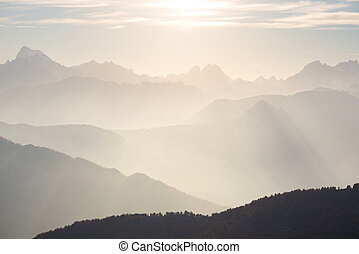 The Alps in soft backlight. Toned mountain range of the Massif des Ecrins National Park, France, arising higher than 4000 m altitude from the alpine arc. Telephoto view at sunset.