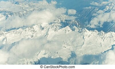 The Alps snowy mountain peaks and clouds on a sunny day, aeial view. 4K stabilized video