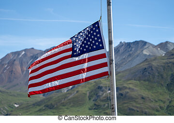 The American Flag flies in front of the Alaska Range mountains at the Eielson Visitors Center in Denali National Park