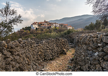 The ancient village of Beli, stone walls on a cloudy day in spring