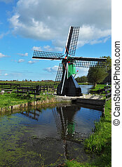 The ancient windmill is reflected in pond.