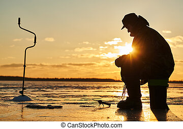 The angler fisherman at ice winter fishing. Sunset