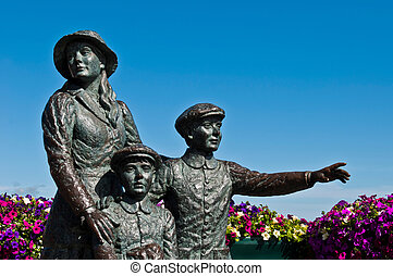 The Annie Moore Memorial, statue of Annie Moore and her two Brothers in Cobh, Ireland (Annie was the first immigrant to the United States to pass through the Ellis Island facility in New York Harbor,)