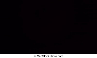The appearance of an unfocused flash and orange light highlights on a black background in 4k motion
