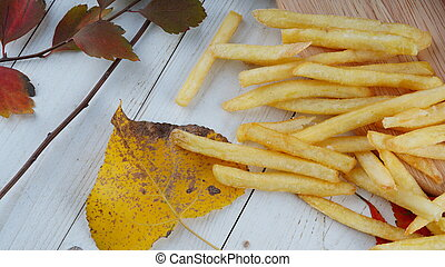 The appetizing french fries are on a wooden board with decoration of autumn leaves.
