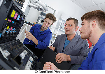 the apprentices fixing a photocopier