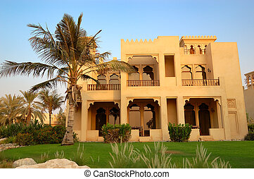 The Arabic style villa and palm during sunset at luxury...