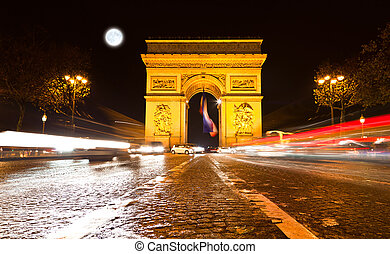 The Arc de Triomphe in Paris illuminated at night.