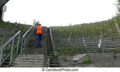 The architect climbs the stairs to assess the condition of...