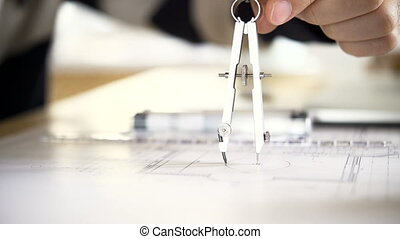 The architect draws a project of an apartment house using a pair of compasses