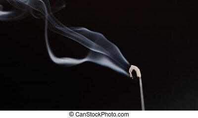 The aromatic stick smokes against a black background close-up. Aromatherapy and Oriental Relaxation 4k