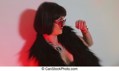 The artist in a black fur coat performs at a kinky party.