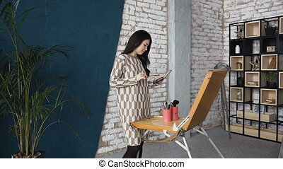The artist on makeup and beauty creates a beautiful face makeup chart using watercolor paper, shadows, lipsticks and blushes. Young woman in dress, in a bright studio draws using board of easel