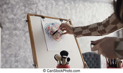The artist on makeup and beauty creates a beautiful face makeup chart using watercolor paper, shadows, lipsticks and blushes using an easel at studio. Young woman in a bright studio draws a face chart using cosmetics for makeup