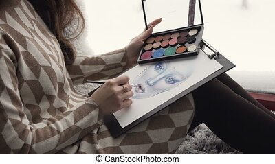 The artist on makeup and beauty sits on the window sill near window and creates a beautiful face makeup chart using watercolor paper, palette shadows, lipsticks and blushes. Face chart