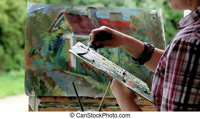 The artist paints a picture.
