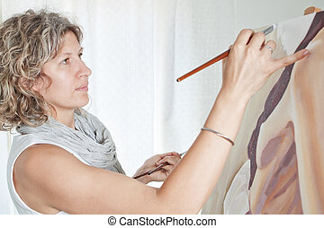 The artist paints a picture of the brushes. Against the background the studio.