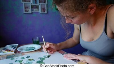 The artist paints on paper at home
