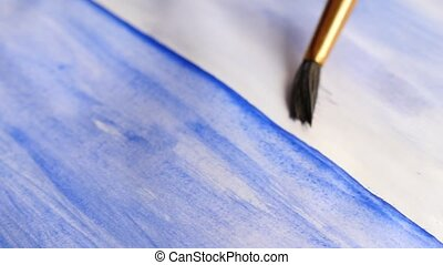 the artist paints paints on a white sheet. close-up of a tassel. 4k, slow-motion shooting
