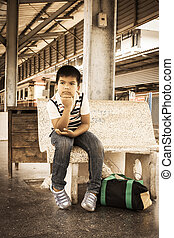 the asian little boyl sit alone at inner train, vintage tone
